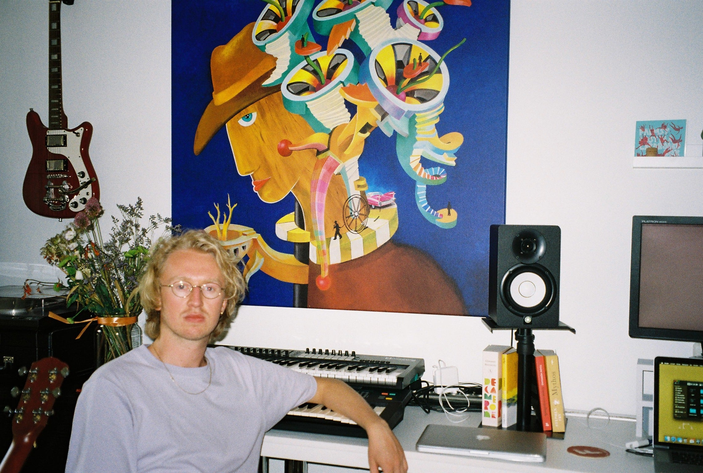 Gilles van Wees in his homestudio, with a painting from his dad